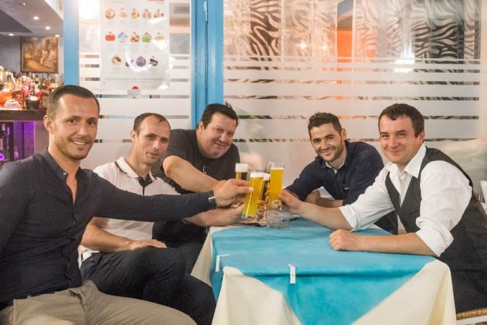 die Mitarbeiter des Restaurant Mykonos am Faaker See sitzen am Tisch und prosten mit einem Glas Bier an
