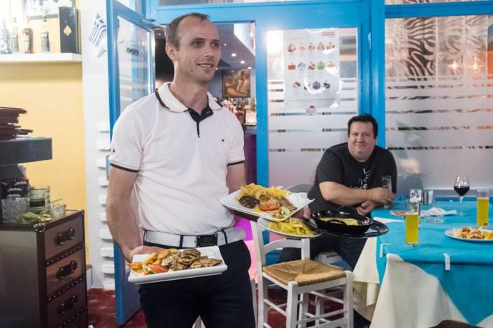 Astrit der Chef serviert Essen auf der Terrasse des griechischen Restaurants Mykonos am Faakersee