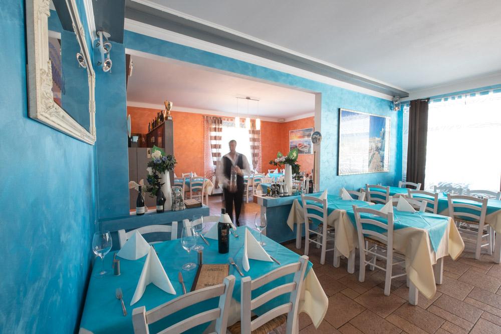Kellner serviert eine Flasche Wein zwischen den gedeckten Tischen im Innenbereich des griechischen Restaurants Mykonos am