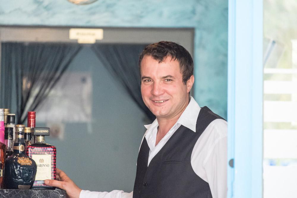 ein männliches Servicepersonal steht in der Türe des griechischen Restaurants Mykonos am Faaker See