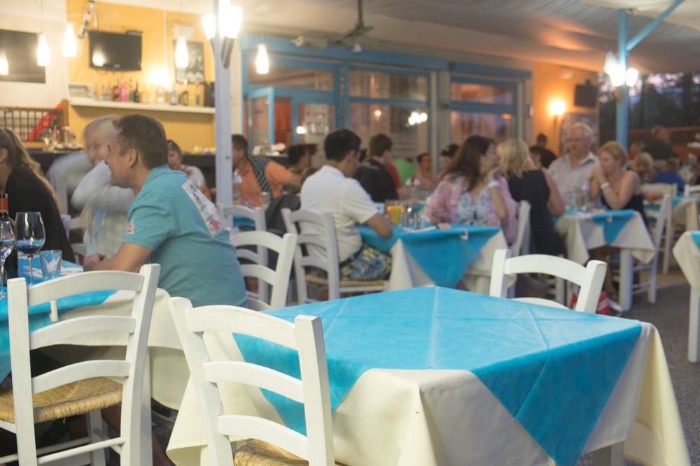 Tische mit Gästen auf der Terrasse vom griechischen Restaurant Mykonos Faakersee beim guten Essen